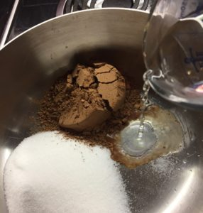 in pot whisk together sugar, cocoa & salt, add hot water